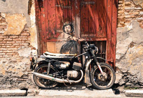 Boy on motorcycle street art mural Penang