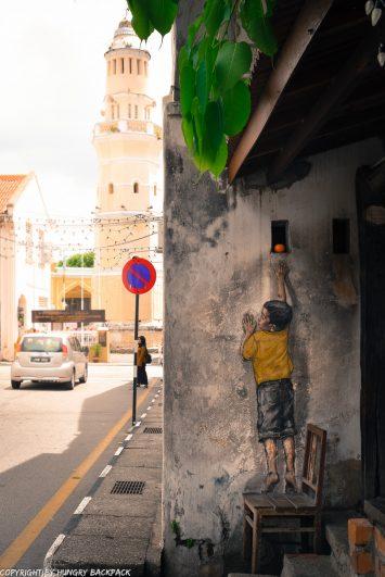 boy on chair reaching street art mural Penang