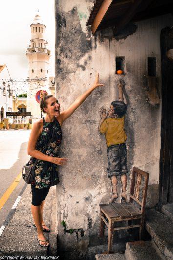 boy on chair street art Penang