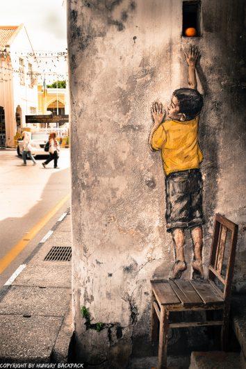 boy on chair street art mural Penang