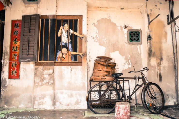 children behind window bao_street art mural Penang