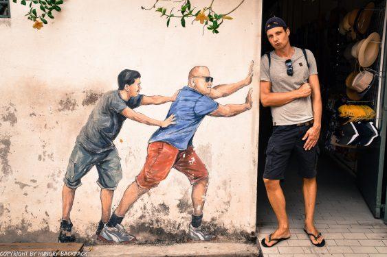 two guys pushing street art mural Penang