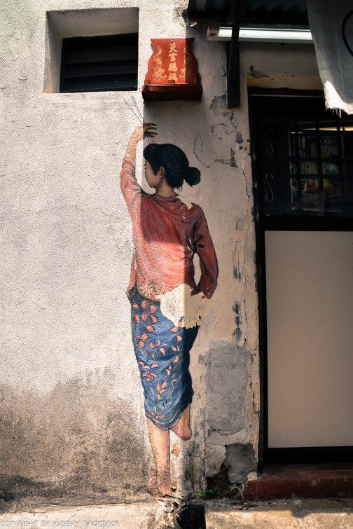woman lighting incense sticks street art mural Penang
