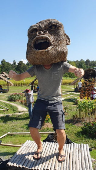 Martin trying on one of the big ape heads at the King Kong village